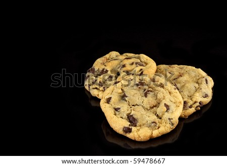 Three Chocolate Chip cookies on black background with copy space