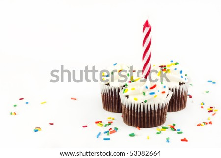 Three chocolate cupcakes with vanilla frosting and sprinkles with one red candle unlit on white background with copy space