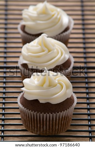 Three chocolate cupcakes with vanilla frosting in a row #97186640