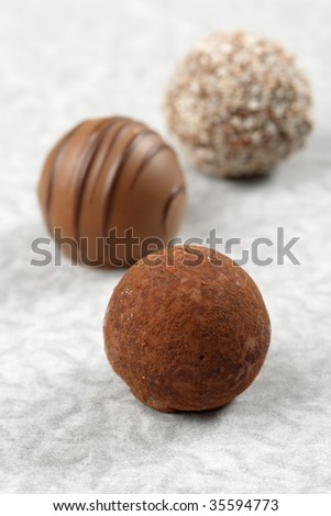 Three chocolate truffles on textured paper.  Very Shallow depth of field, focusing on first truffle.