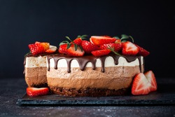 Three chocolates cake with chocolate drips on a black background. Layered cake with milk, black and white chocolate souffle decorated with strawberries on top. Confectionery background with copy space