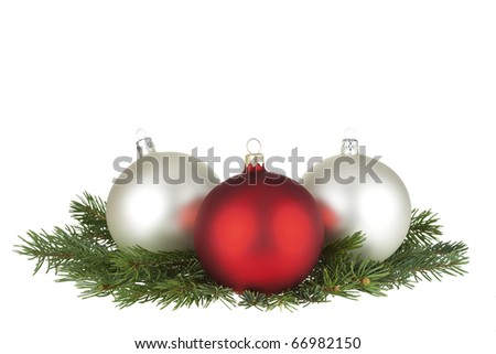 Three Christmas balls and spruce isolated on white.