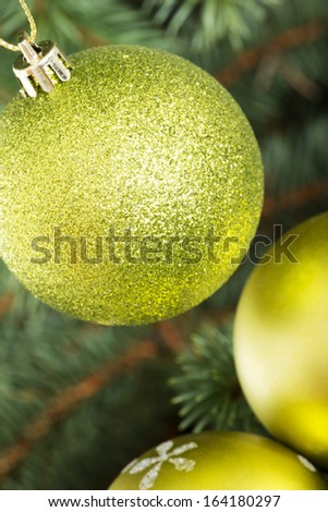Three christmas balls hanging on a green tree.