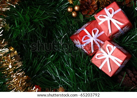 Three Christmas presents placed on green fir with golden decoration chain and copy space