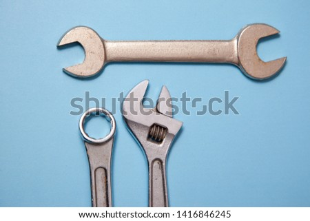 Three chrome spanners or wrenches displayed against a blue background  #1416846245