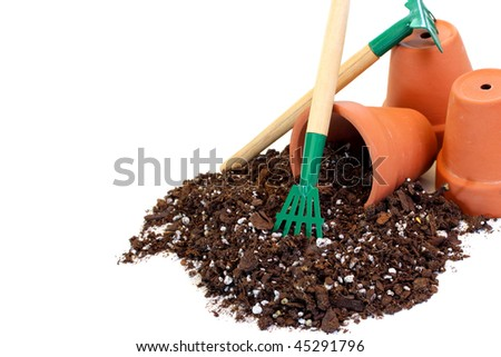 Three clay flowerpots with top soil and a rake on a white background with copy space.