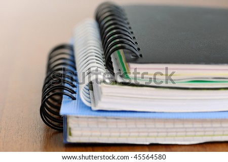Three closed spiral notebooks in a pile on the wooden table with shallow depth of field