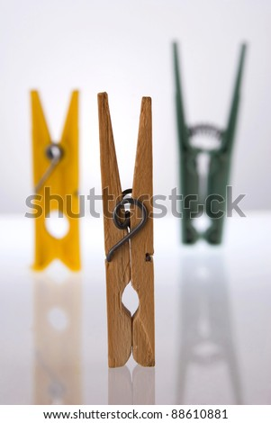 Three clothes peg composition with its reflection on white background.