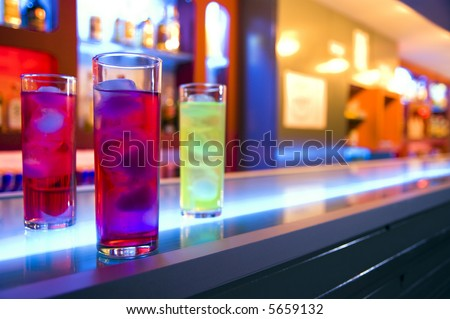 Three cocktail drinks on a bar, blurry color background