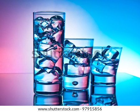 Three cocktails in different glasses on pink and blue background