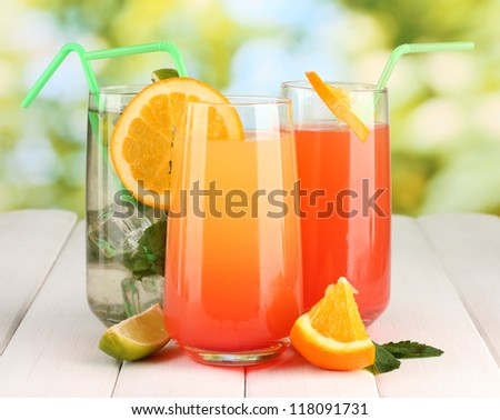 Three cocktails on wooden table on bright background