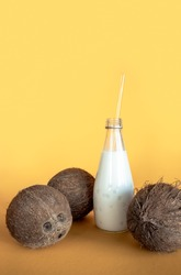 Three cocos nuts with a glass bottle of a coconut milk at yellow background. Natural tropical fruit and drinks for vegan menu or keto dieting.