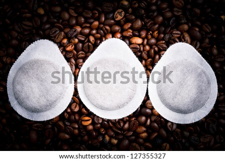 three coffee capsule and coffee beans