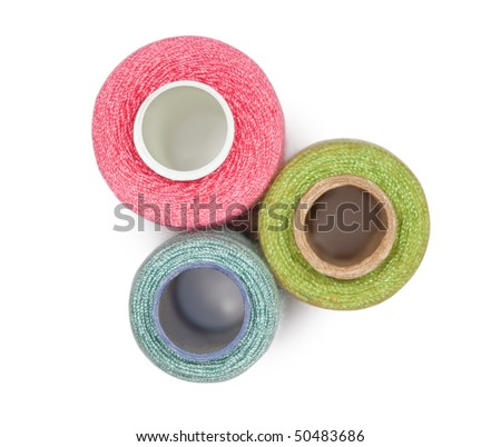 Three coils with multi-coloured sewing threads isolated on white background, top view
