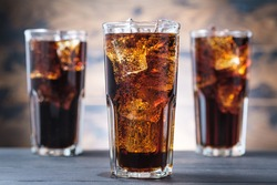 Three cola glass with ice cubes and bubbles. Cold sweet drink on wooden background