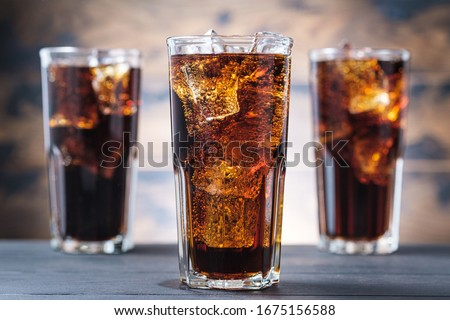 Three cola glass with ice cubes and bubbles. Cold sweet drink on wooden background Stockfoto ©