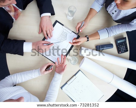 Three colleagues are discussing a round-table draft house #73281352