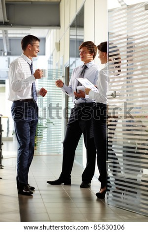 Three colleagues communicating and laughing in office