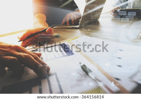 three colleagues interior designer discussing data and digital tablet and computer laptop with business document and graphics design diagram on wooden desk as concept