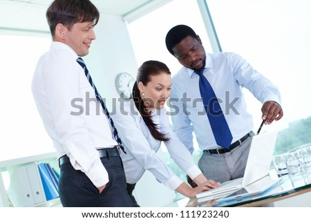 Three colleagues working with laptop at meeting