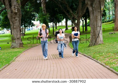 three college students running in campus