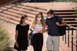 Three college students wearing face masks chatting while walking outdoors in the campus during the Coronavirus pandemic.