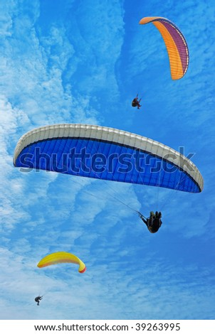Three color flying parachutes in blue sky