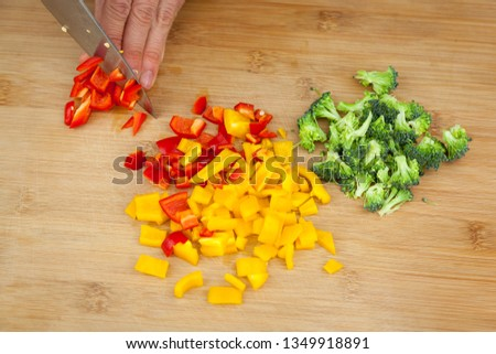 Three color peppers sliced in small dices and chopped broccoli being cut by a man hand on a wooden table. Vegetarian flavor and nutrition basics. Healthy and veggie cooking actions.