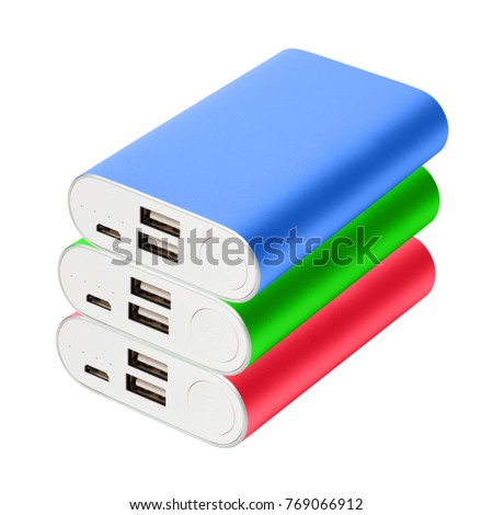 Three color portable chargers lie on one on one isolated on white background.  Green, red, blue powebanks for charging gadgets: phones, tablets, etc.