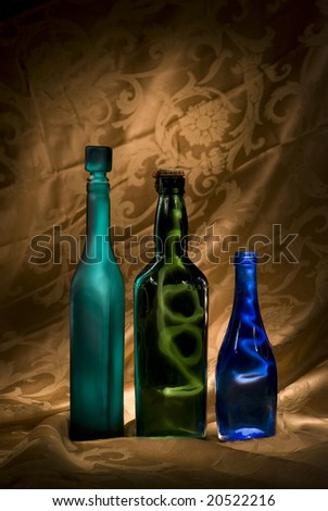 Three colored bottles lit creatively to contain the light against a dramatic golden background.