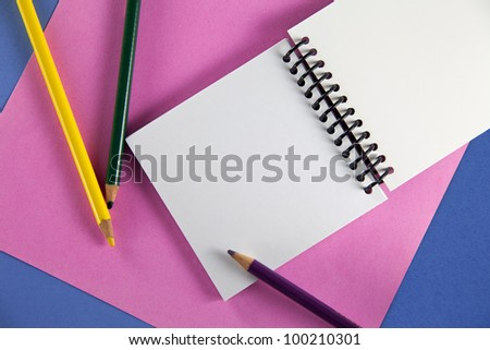 Three colored pencils with petite spiral notebook on pink and blue paper