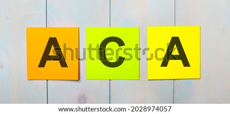 Three colored stickers with the text ACA on a light blue wooden background Imagine de stoc ©