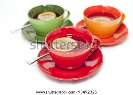 Three colored tea cups with tea and lemon