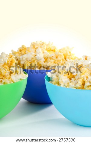 Three colorful bowls filled with hot buttered popcorn. Shallow dof, popcorn in two front bowls in focus. INSPECTOR: Surface the bowl is sitting on is paper with rag content. That's not noise. Thanks.