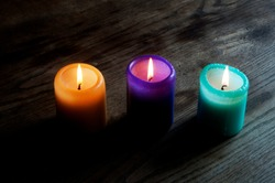 Three colorful candles on a wooden table