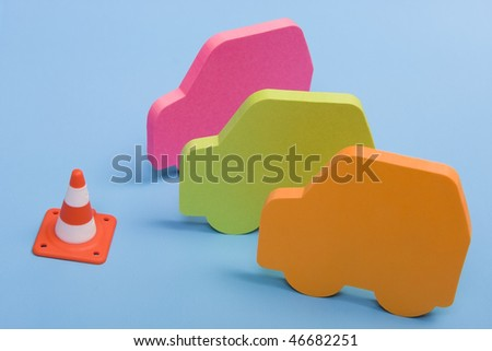 Three colorful cars on front of a signaling cone on a blue background