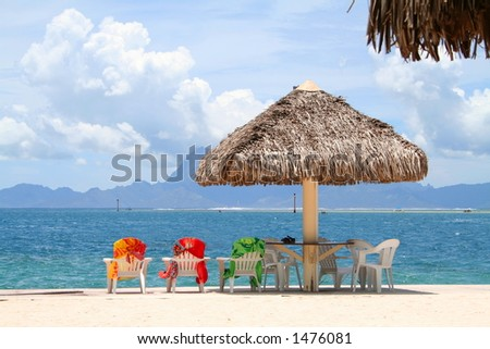 Three colorful chairs aligned on a beach in Tahiti, French Polynesia
