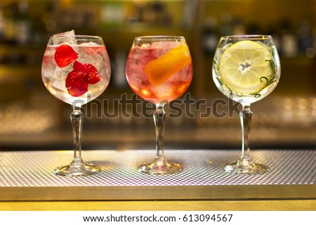 Three colorful cocktails in large wine glasses in a classic bar environment with dozens of blurry liquor bottles in the background. #613094567