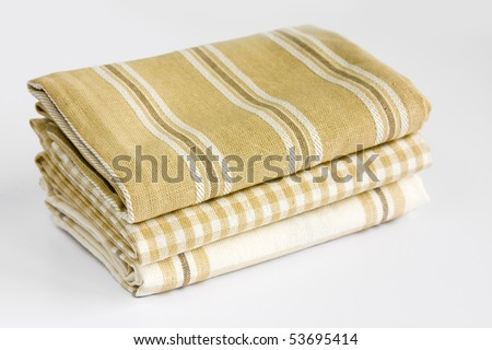 Three colorful cotton kitchen towels folded and stacked