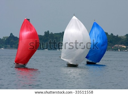 Three colorful cruising sailboats
