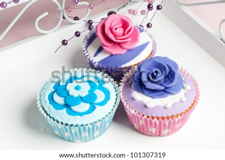 Three colorful cupcake with flowers on a plateau