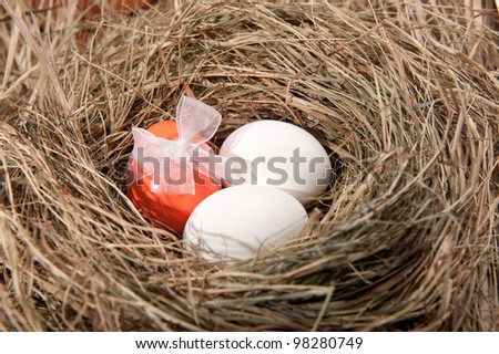 Three colorful Easter eggs in straw nest