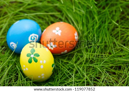 Three colorful Easter eggs on a fresh green grass