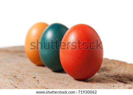 Three Colorful Easter Eggs on an Old Board