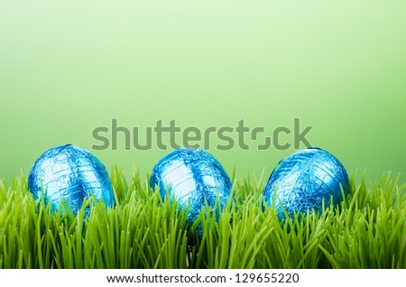Three colorful foil wrapped Easter eggs on grass