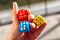 Three colorful game dice held in hand showing number six, three sixes. Holding 3 colored dice between fingers, lucky throw, luck in gambling, winning abstract concept, success, good odds symbolic