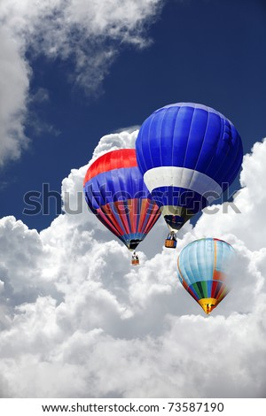Three colorful hot air balloon floating between a dramatic cloud formation in the sky.