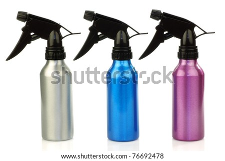 three colorful metal spray bottles on a white background