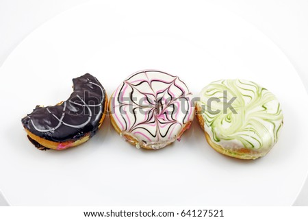 Three colorful pattern donut with one with a bite on a white plate.