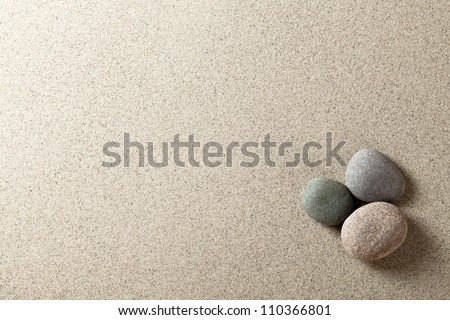 Three colorful round stones on sand background